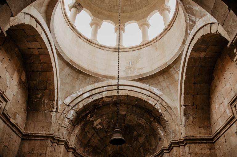 Die Kuppel einer Kirche von innen mit einer Glocke in der Mitte.