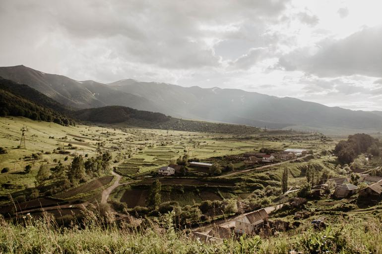 Man sieht eine grüne Landschaft von einem Berg aus. Mit Feldern und Häusern darauf.