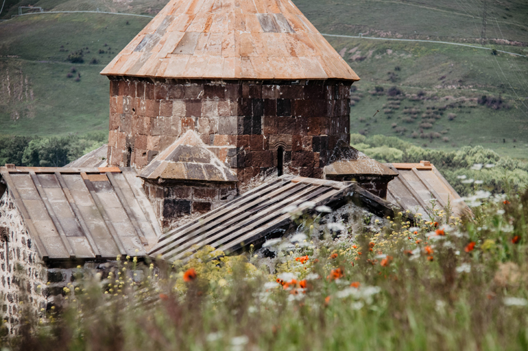 Eine Kirchendach mit Blumen auf einem Hügel davor.