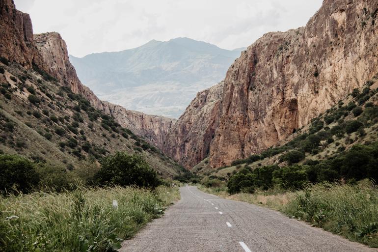 Eine Schlucht mit Bergen, zwischen der eine Straße durchführt.