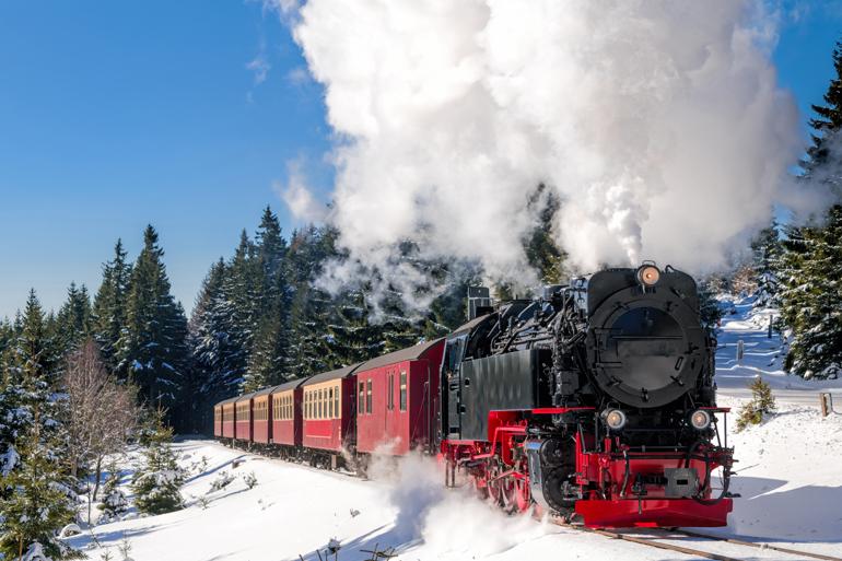 Ein Zug der durch den Schnee fährt.