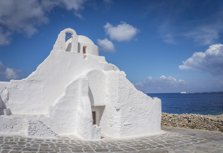 Eine weiße Kirche mit dem Meer im Hintergrund.