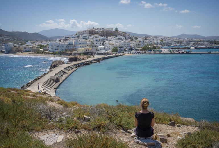 Eine Frau sitz am Boden von einem Aussichtspunkt und schaut auf das Meer und die Stadt hinunter.