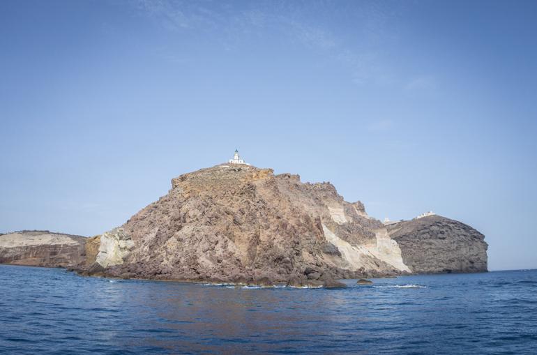 Ein Felsen vom Wasser aus mit einer Kirche darauf.