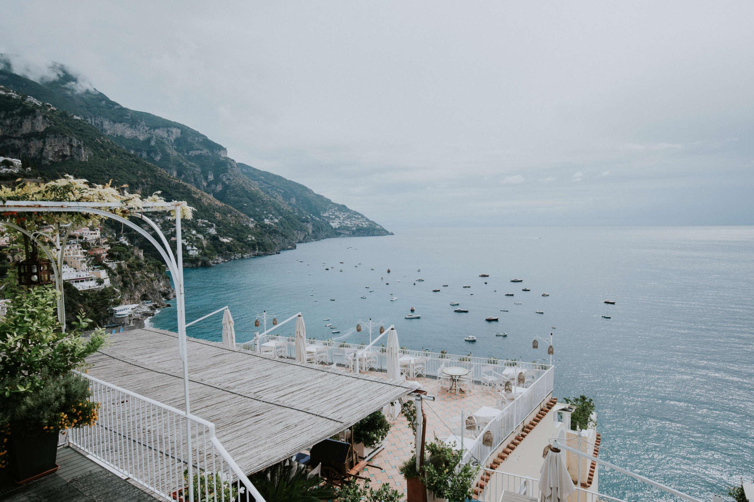 Von einem Balkon aus sieht man auf das Meer in dem viele Boote schwimmen..