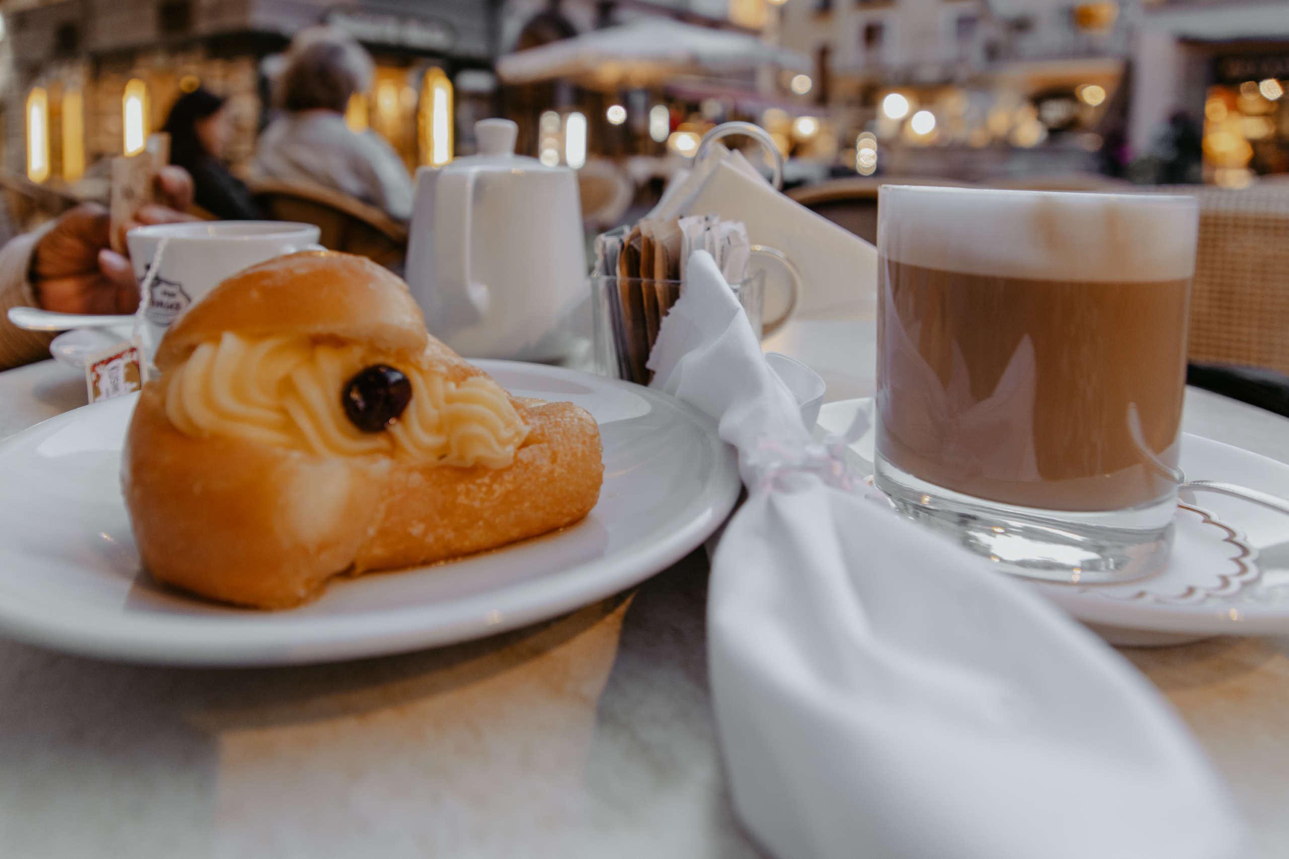 Ein Gebäck auf einem Teller mit einem Kaffee.