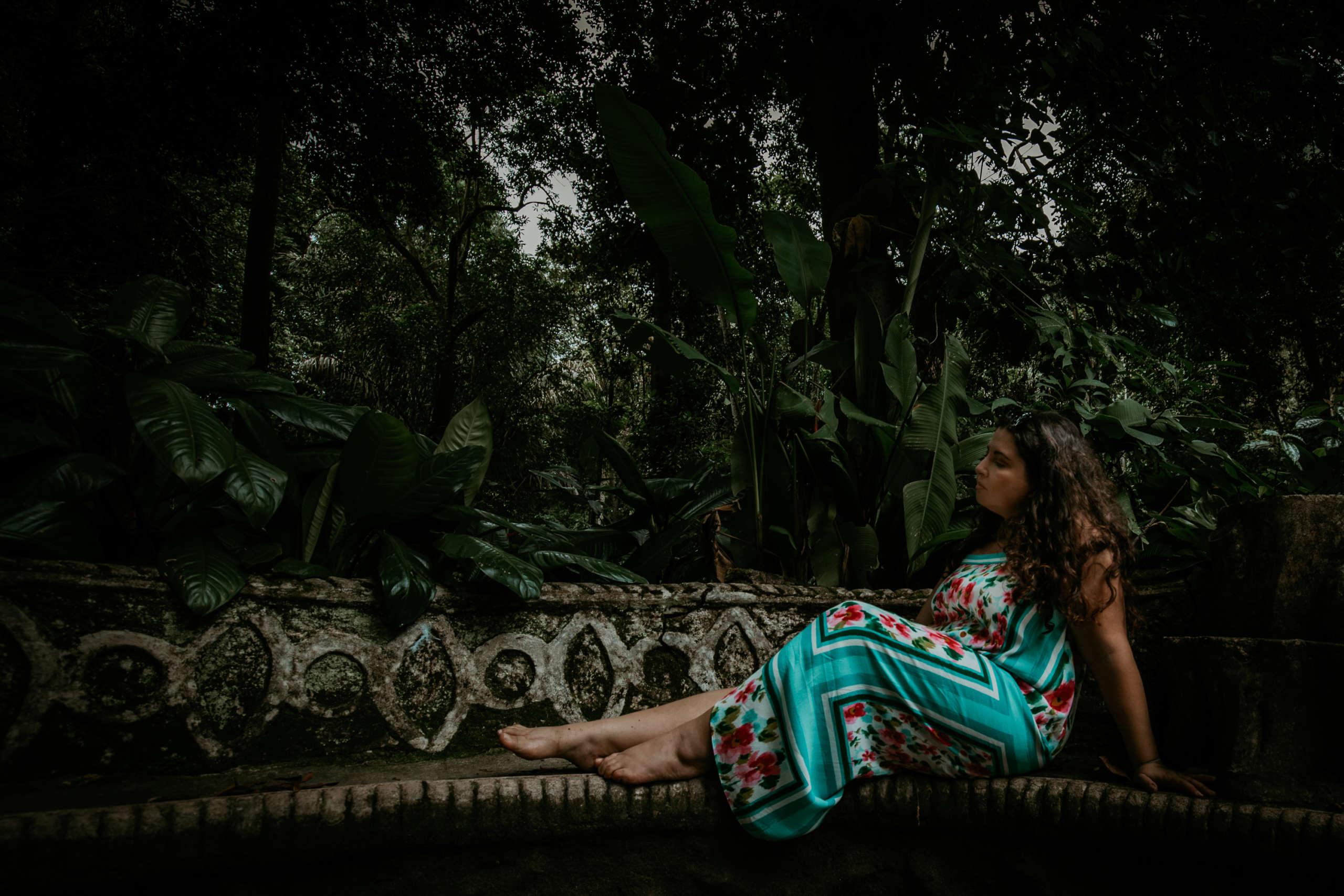 Eine Frau die auf einer Bank unter Bäumen sitzt.