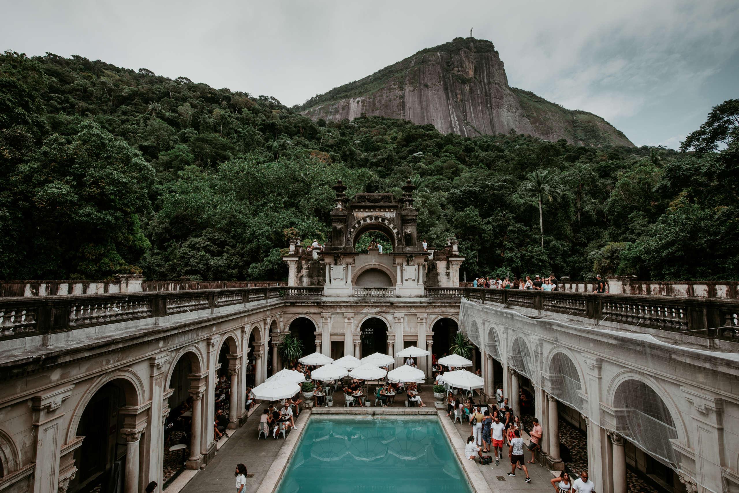 Ein Pool mit einem Cafe und einem Berg im Hintergrund.