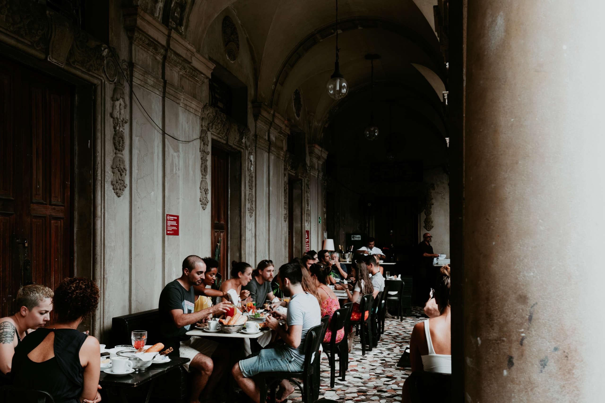 Menschen die an Tischen in einem Cafe sitzen.