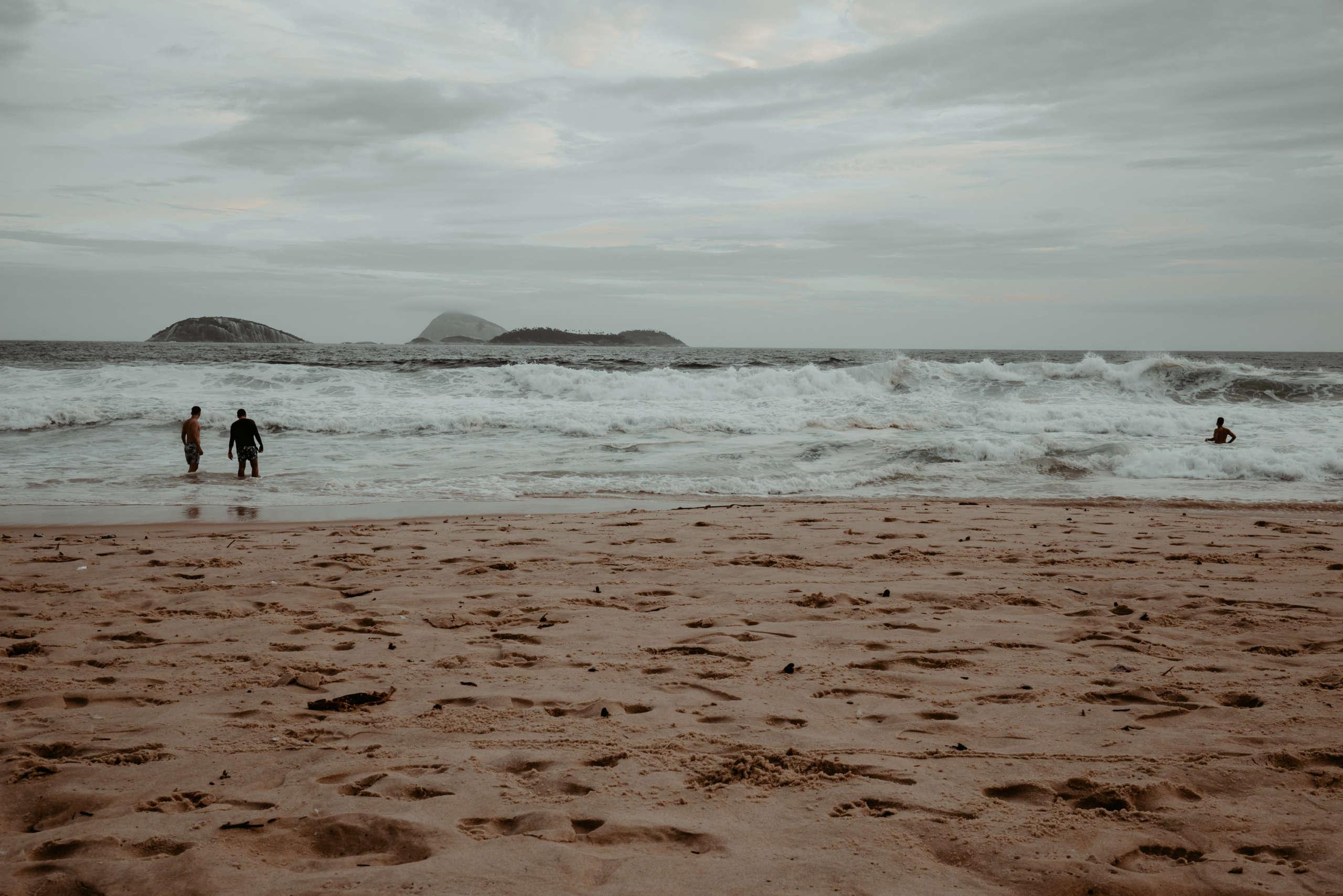Ein Strand mit Personen im Meer.