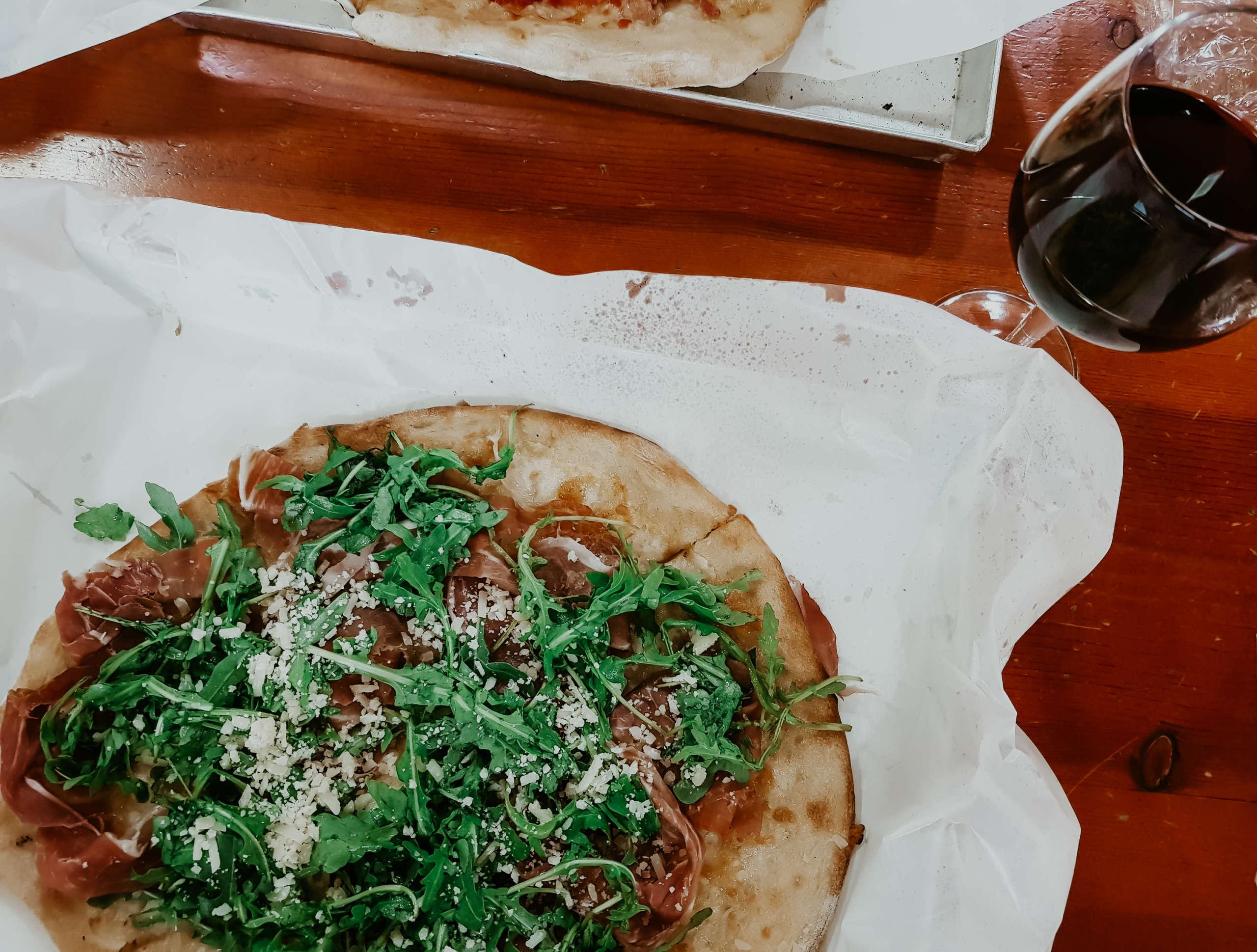 Eine Pizza mit einem Glas Rotwein daneben.
