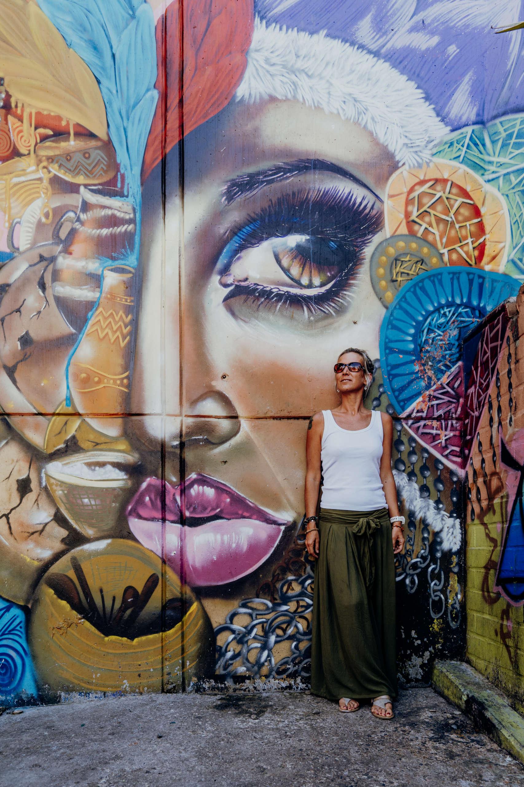 Eine Frau die vor einer Wand steht auf der ein Kopf abgezeichnet ist.