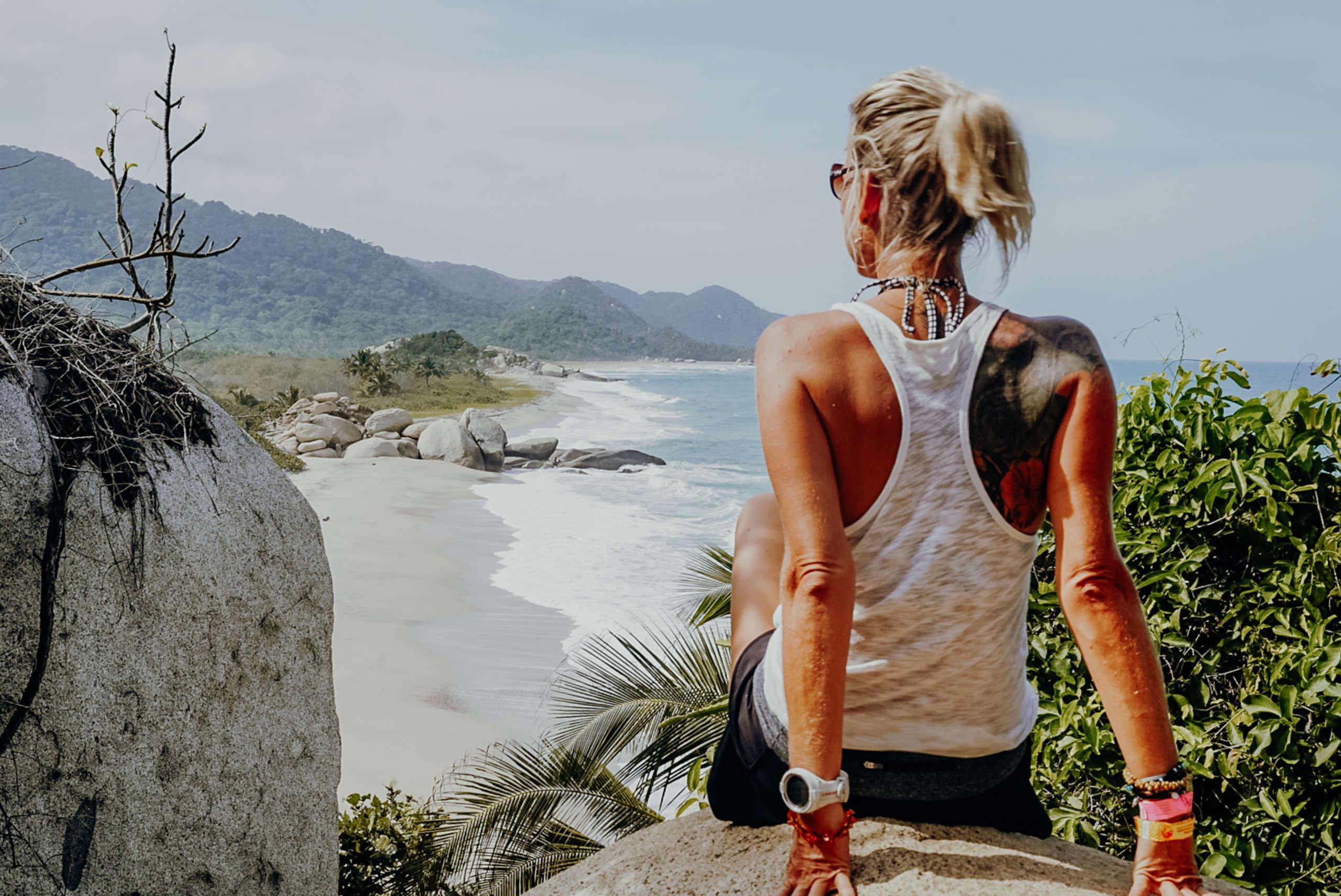 Eine Frau die auf einem Fels sitzt mit dem Meer im Hintergrund.