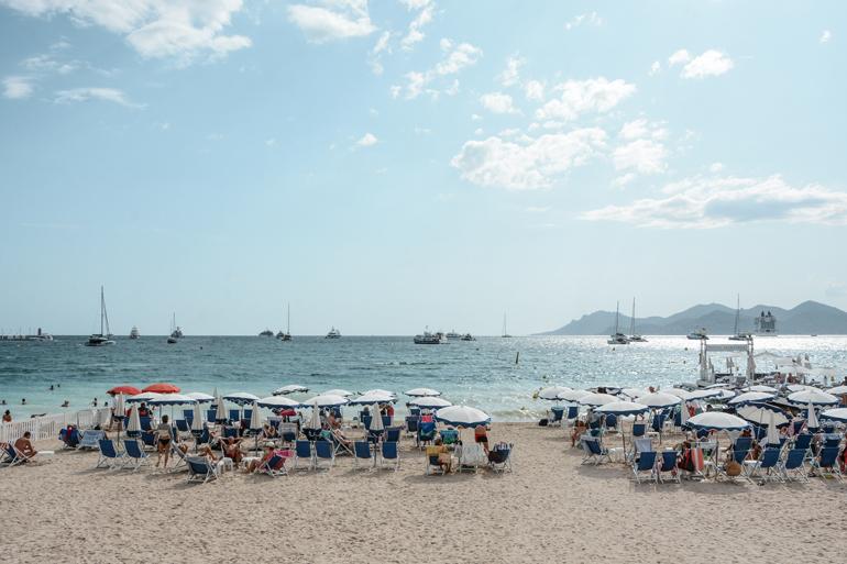 Ein Strand mit Liegestühlen und Sonnenschiermen.