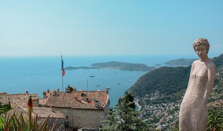 Eine Statue die auf einem Berg steht und das Meer im Hintergrund ist.