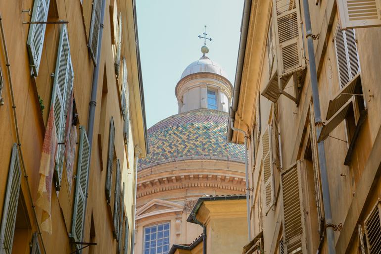 Eine Gasse mit Häusern und einem Kirchen Dom.