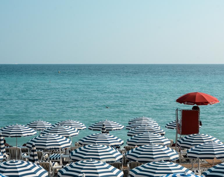 Blau - weiße Sonnenschirme stehen am Strand.