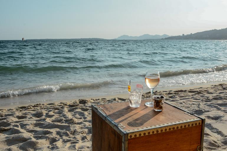 Ein kleiner Tisch der am Meer steht mit zwei Getränken drauf.