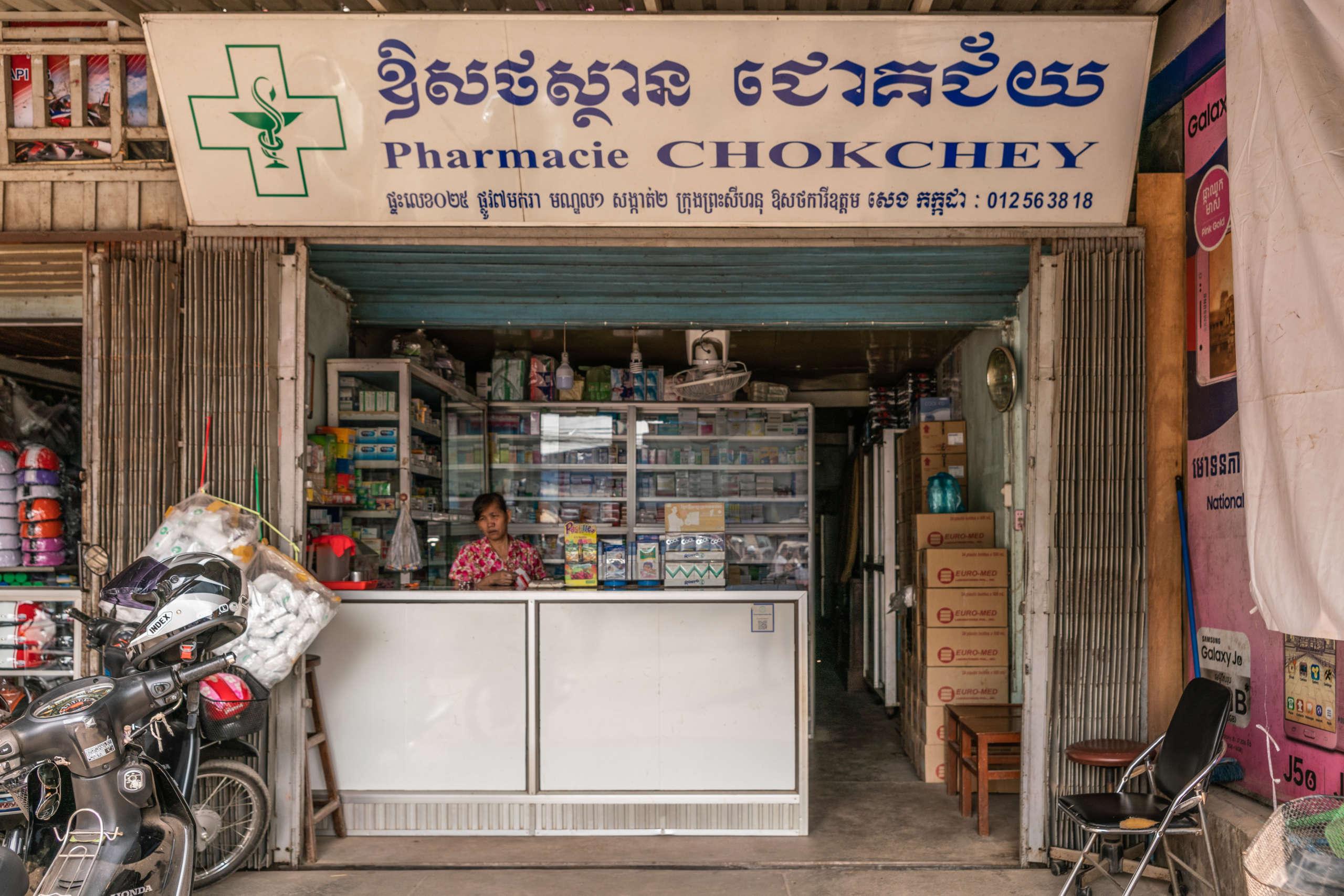 """Eine Frau steht hinter einem Apothekentresen eines offenen Geschäfts mit Apothekenzeichen und der Aufschrift """"Pharmacie Chokchey"""""""
