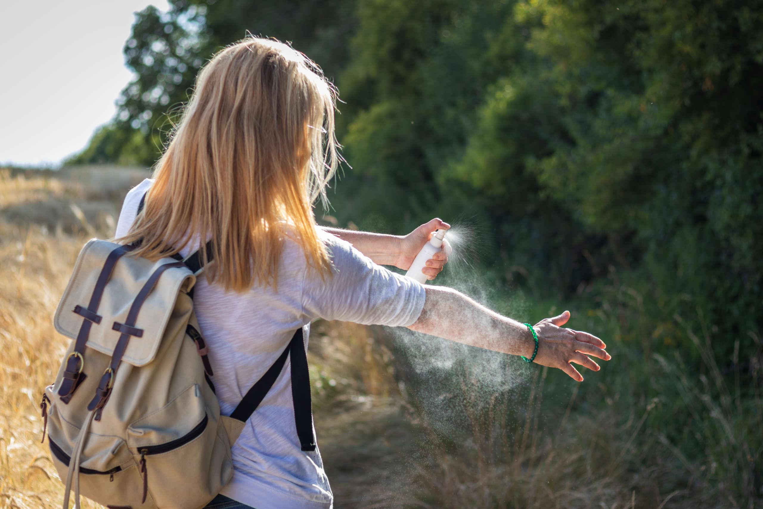 Eine Frau besprüht sich mit Insektenspray.
