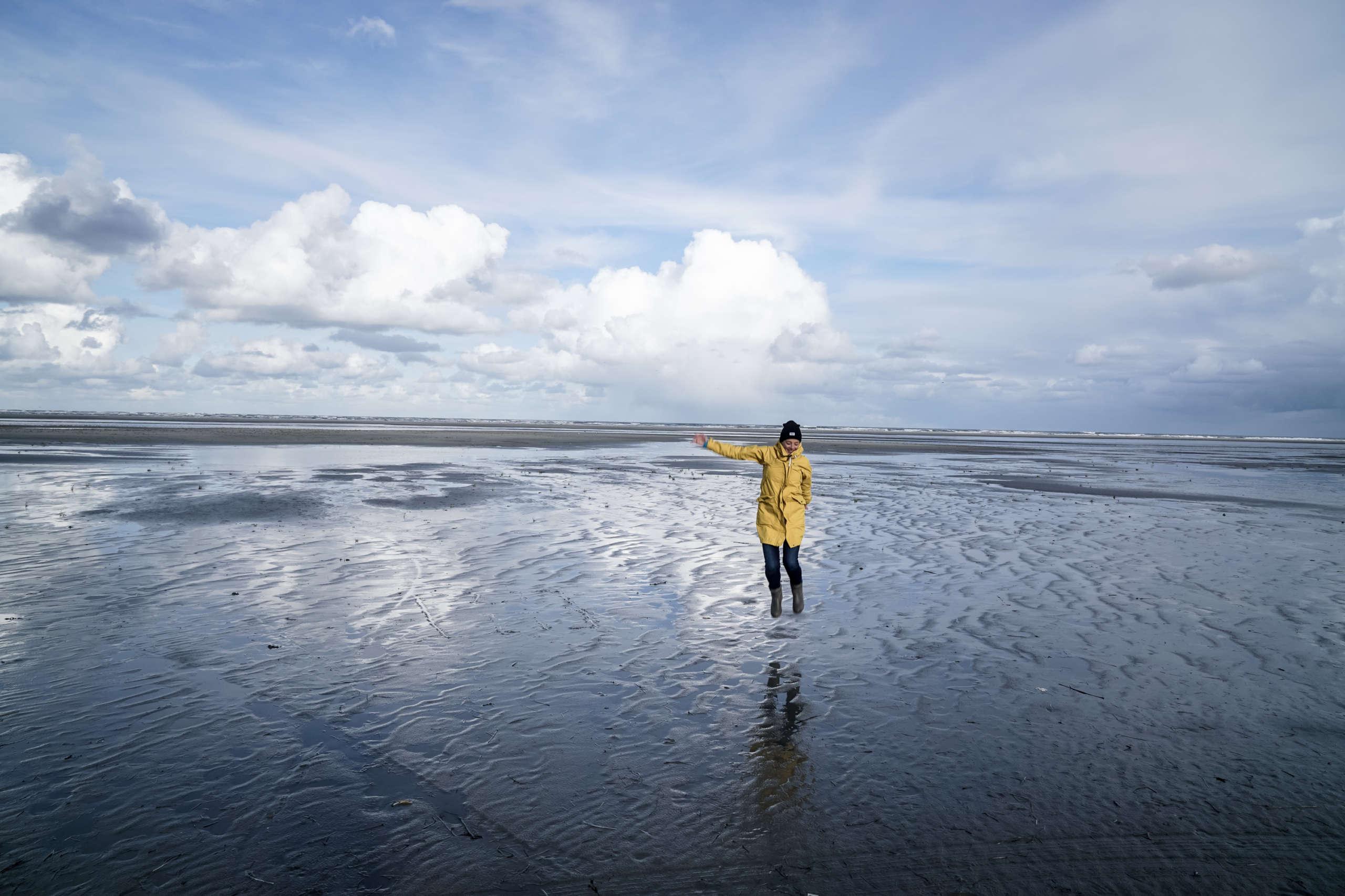 Eine Frau im gelben Regenmantel steht bei Ebbe auf dem Wasser auf der Insel Ammeland in den Niederlanden und streckt den Arm heraus