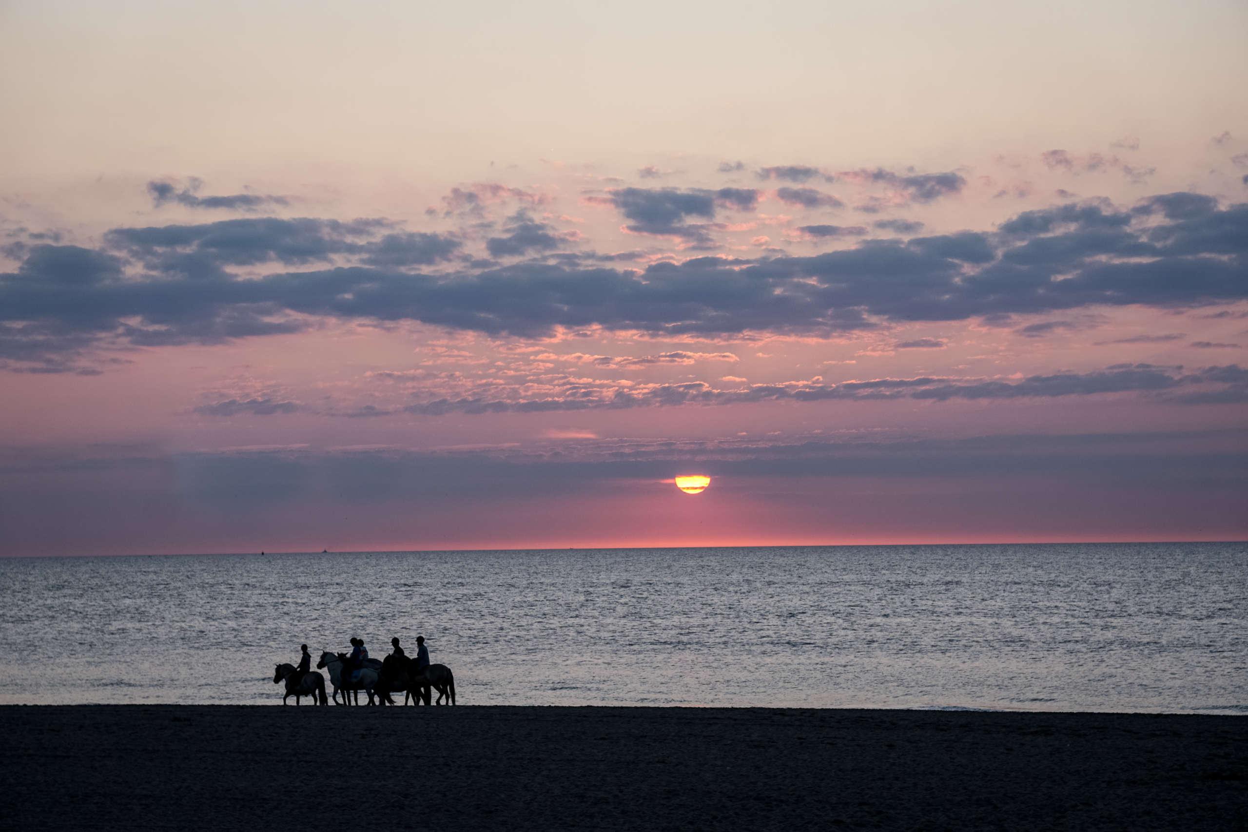 Sonnenuntergang am Meer, Reiter reiten den Strand entlang