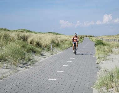 Eine Frau fährt auf einem Fahrradweg Rad, rechts und links von ihr befinden sich Sandanhäufungen auf denen Gestrüpp wächst