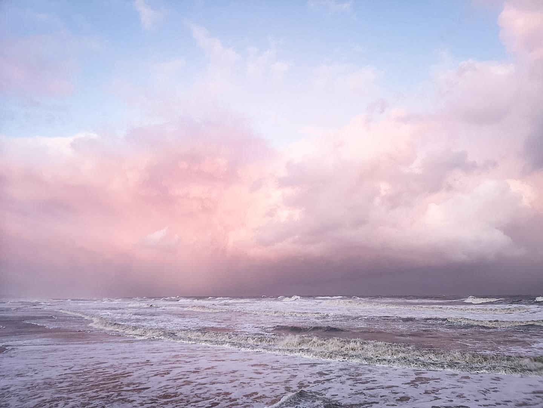 Die seichte Nordsee mit leichtem Wellengang, dahinter der sich pink färbende Himmel