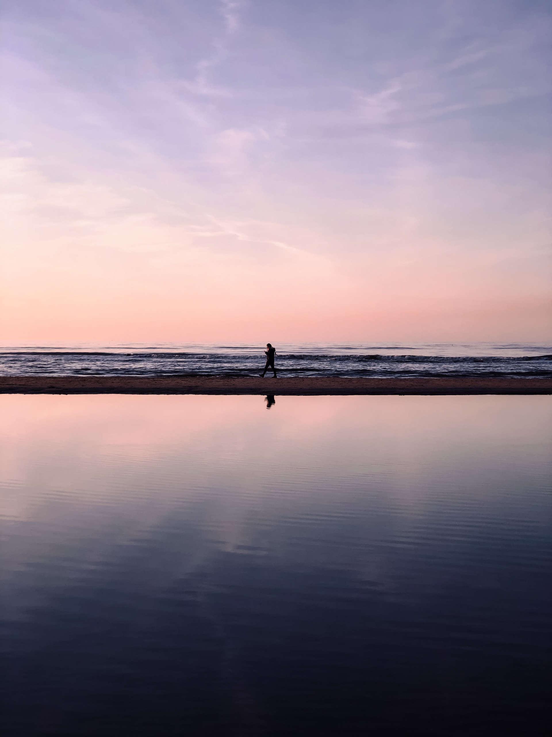 Lila und pink gefärbter Himmel, darunter das Meer und eine kaum erkennbare Person, die den Strand entlang spaziert