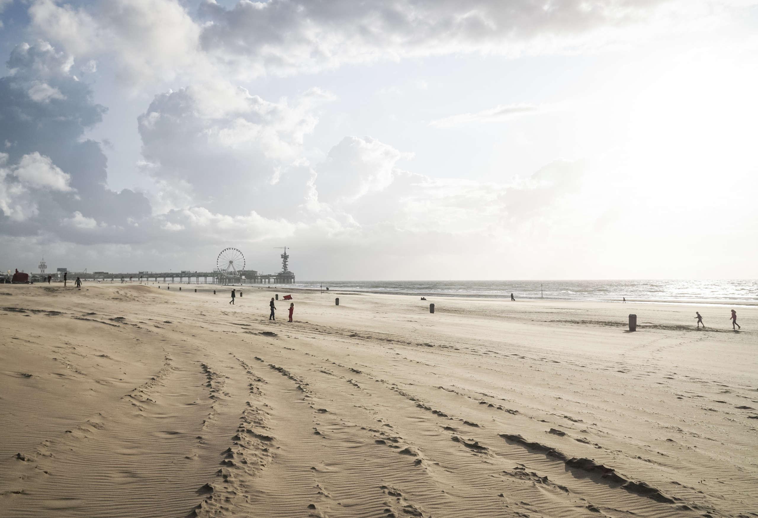 Ein weitläufiger Strand in Scheveningen an der niederländischen Küste, in der Ferne befindet sich ein Pier mit einem Riesenrad.