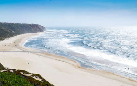 Strand an der Atlantikküste in Portugal mit hohen Wellen lockt Surfer aus aller Welt an.