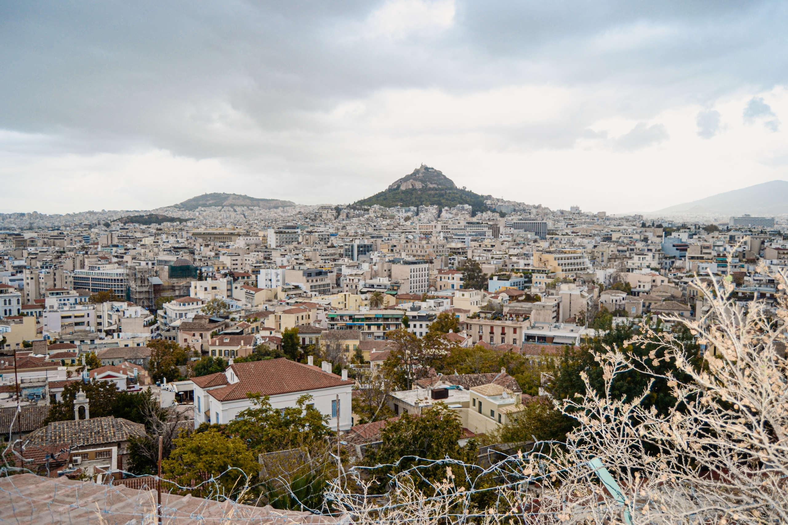 Skyline von Athen, Blick über Häuser und einen Berg i Hintergrund.