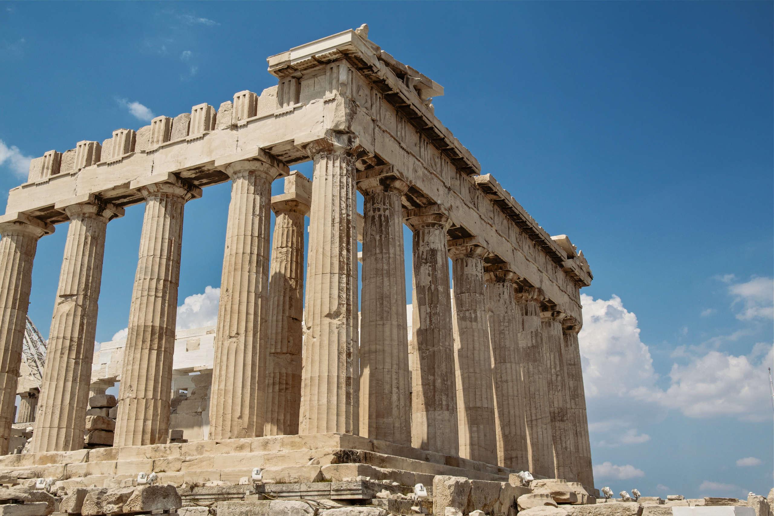Ein Tempel auf der Akropolis in Athen aus der Froschperspektive, darüber blauer Himmel.