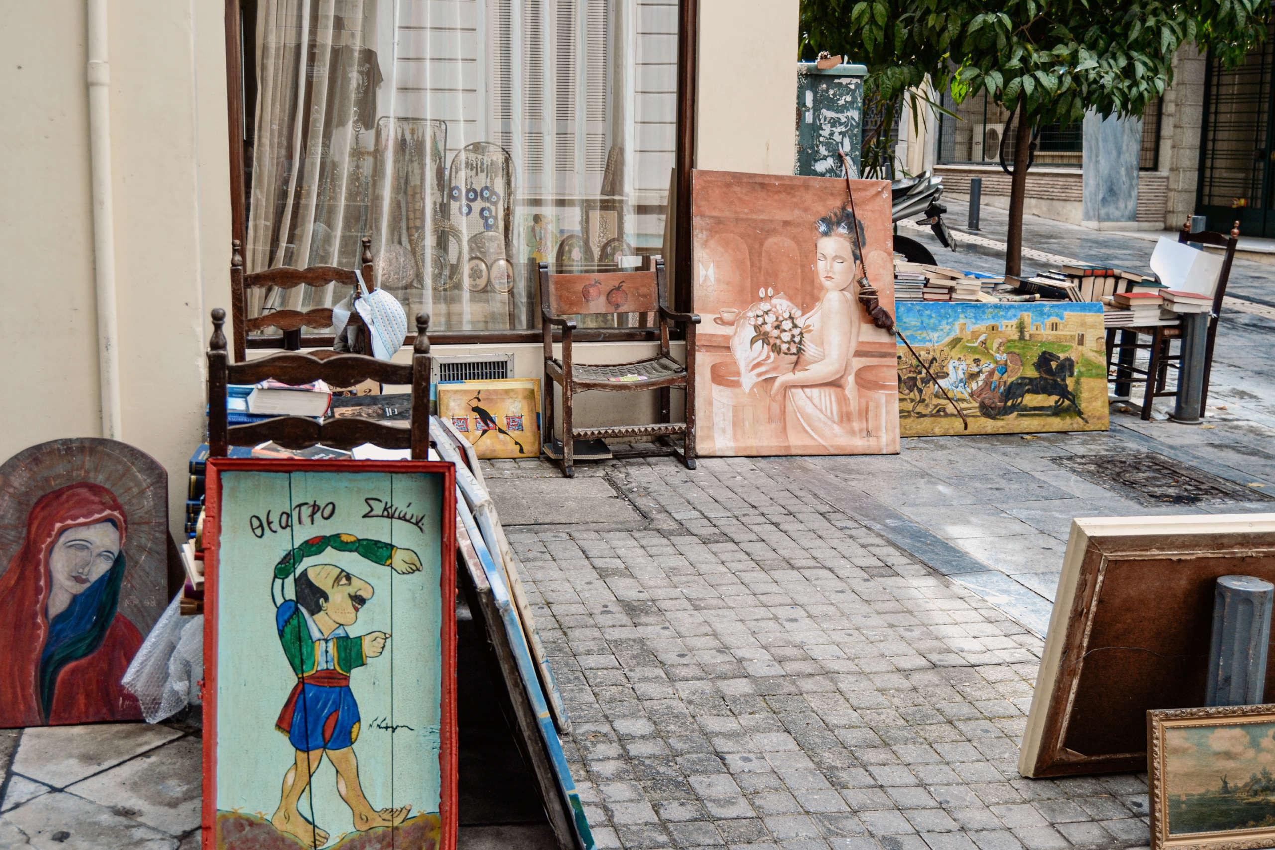 Gemälde lehnen an einer Hauswand auf einem Flohmarkt in Athen.