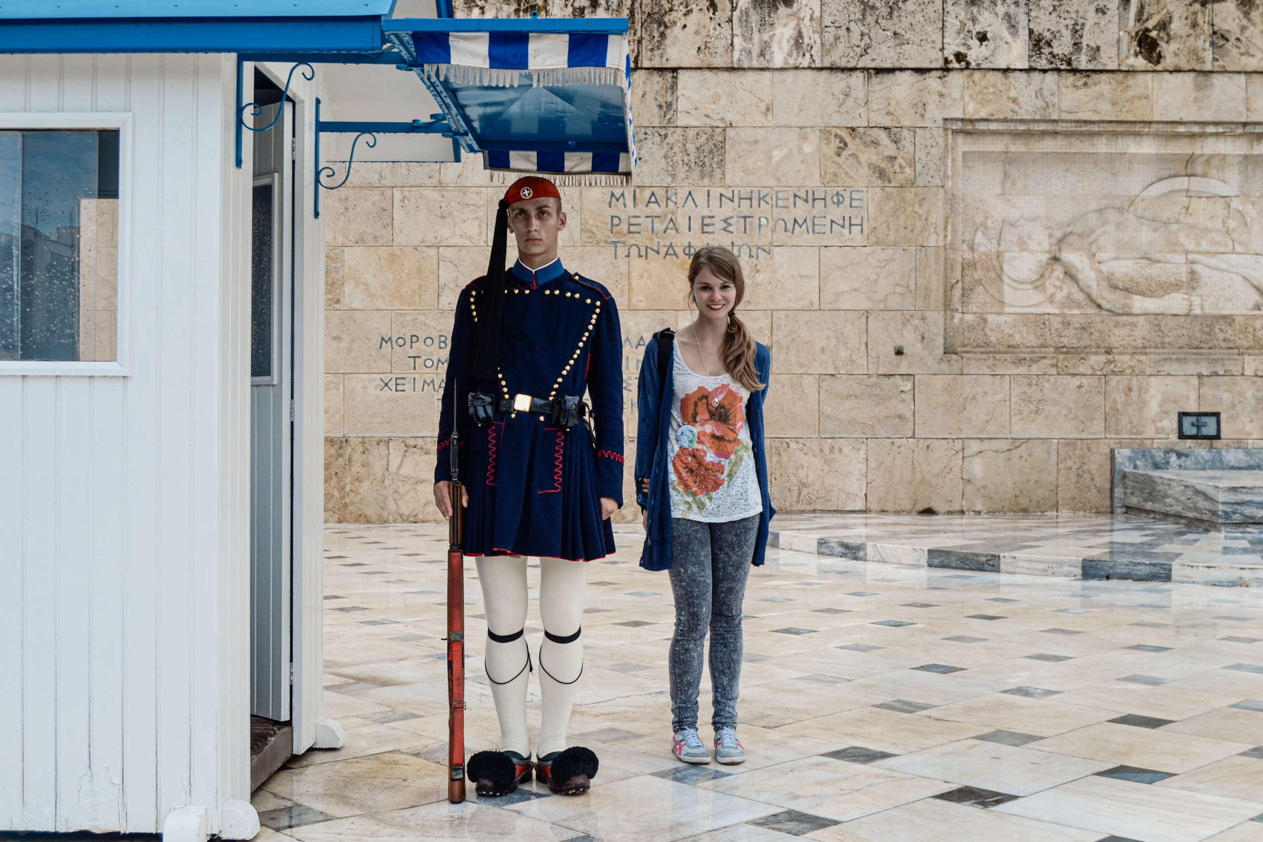 Ein Wächter im traditionellen Kostüm vor dem griechischen Parlament in Athen, neben ihm postiert eine lächelnde Frau für das Foto.