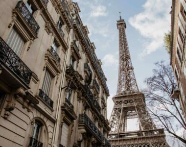 Netter Ausblick auf einem Streifzug durch Paris: Zwischen zwei Wohnhäusern fällt der Blick auf den Eiffelturm, der in den blauen Himmel ragt.