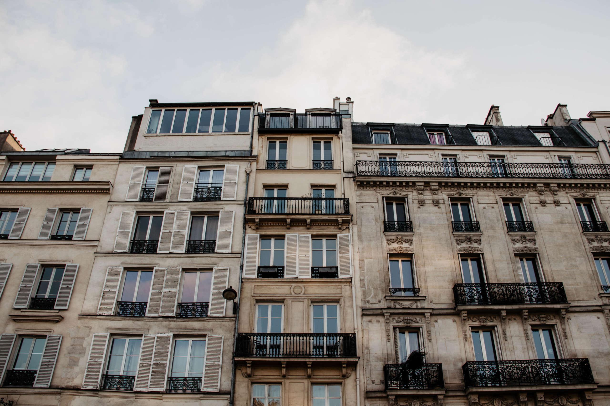 Imposanten Häuserfassaden mit verschnörkelten Balkongeländern begegnen Besuchern an vielen Ecken in Paris.