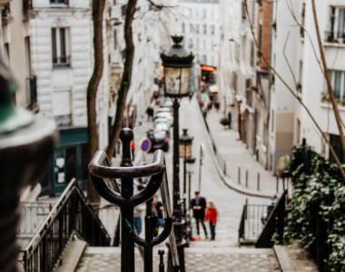 Treppenstufen führen auf den Montmartre, im Hintergrund eine der kleinen, einladenden Gassen von Paris.