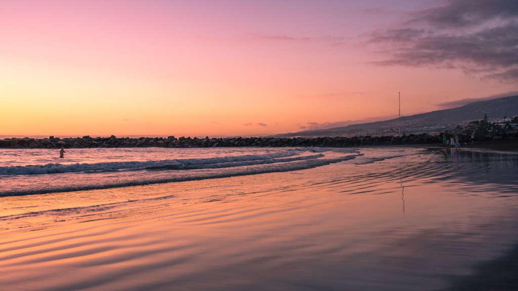 Ein unvergessliches Erlebnis auf Teneriffa: Zum Sonnenuntergang färbt sich der Himmel über dem Strand von Playa de Las Americas in den schönsten Rottönen.