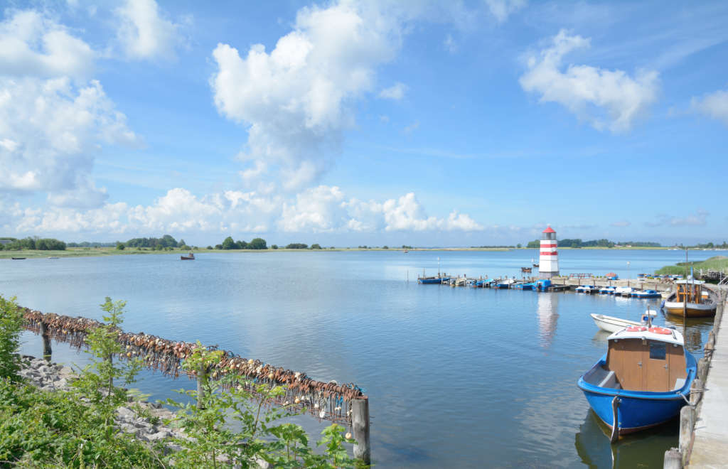 Auf der Ostseeinsel Ummanz liegen kleine Fischerboote und ein Mini Leuchtturm in der Bucht.
