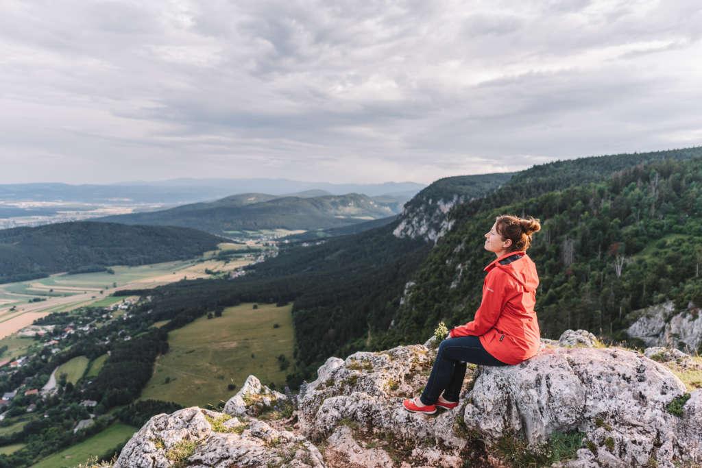 Bloggerin Melanie sitzt auf einem Felsenvorsprung im Naturpark Hohe Wand, der von Wien aus nur eine Stunde Autofahrt entfernt ist.