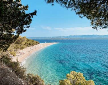 """Blick durch Bäume auf den Sandstrand """"Goldenes Horn"""" in Kroatien, der Reisende mit seinem türkisblauen Meer zum Baden einlädt."""