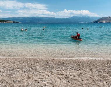 Blick vom Sandstrand Vela Plaža aufs Meer in Kroatien. Auf und in dem Wasser sind viele Wassersportler und Schwimmer unterwegs.