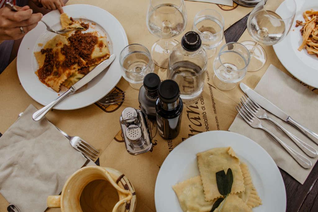 Ein gedeckter Tisch mit italienischen Pasta-Spezialitäten auf weißen Tellern, dazu gibt es italienischen Weißwein.
