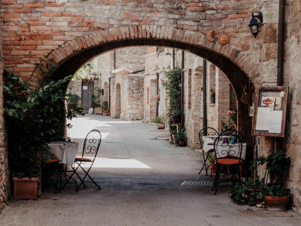 Im Schatten des Torbogens einer Mauer im italienischen Ort San Quirico d'Orcia stehen Tisch und Stühle des Retaurants.