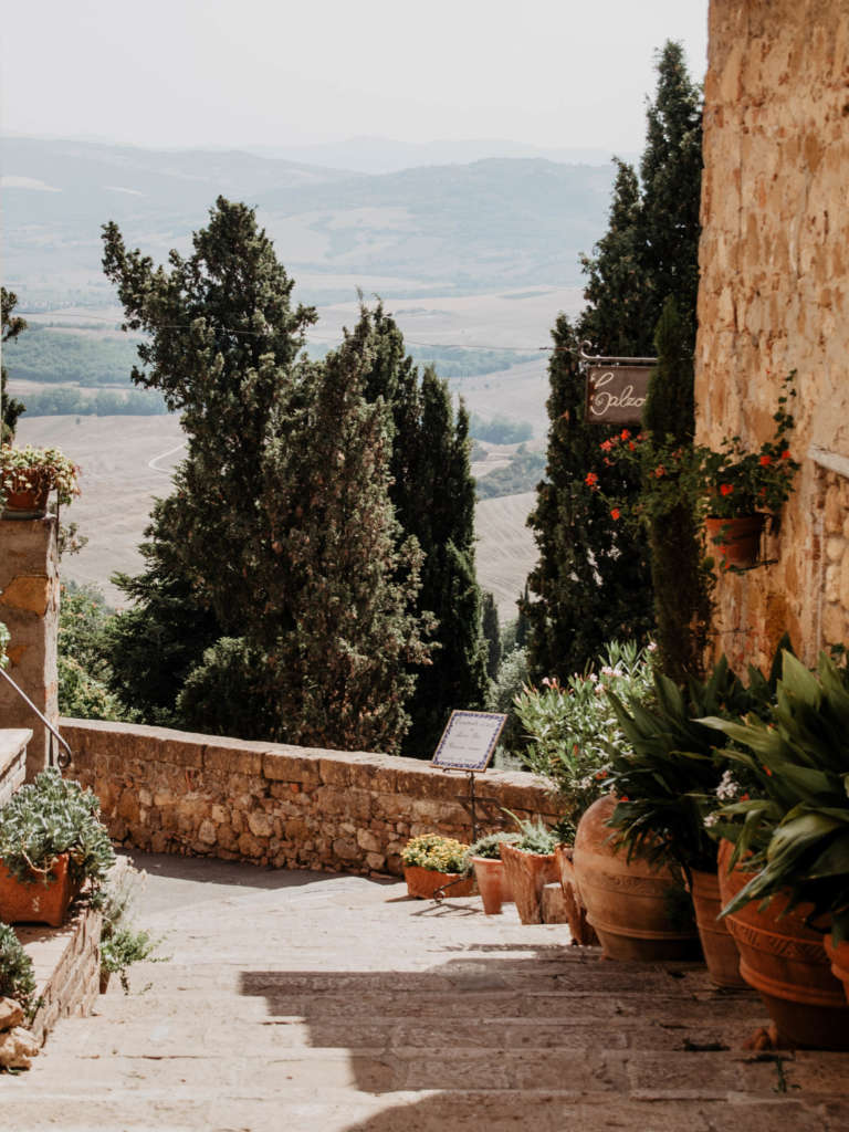 Eine Terrasse mit bepflanzten Blumenkübeln und Aussicht auf die Hügel der Toskana.