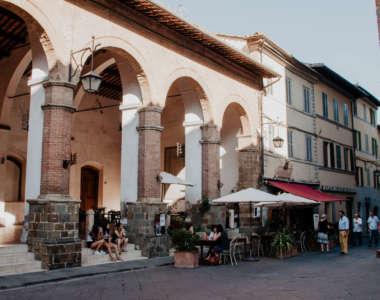 Geheimtipp für Toskana-Reisende: Das kleine Dörfchen Montalcino - hier Arcaden, unter denen ein paar Jugendliche sitzen, daneben ein gemütliches Café mit Sonnenschirmen auf der Außenterrasse.