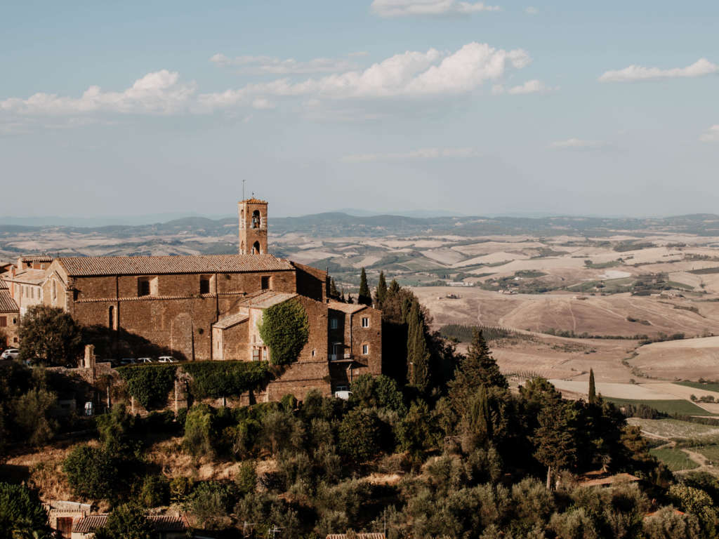 Auf einer Erhöhung befindet sich eine Festung, die von Bäumen umgeben ist - im Hintergrund die weite toskanische Landschaft mit ihren Hügeln und Zypressen.