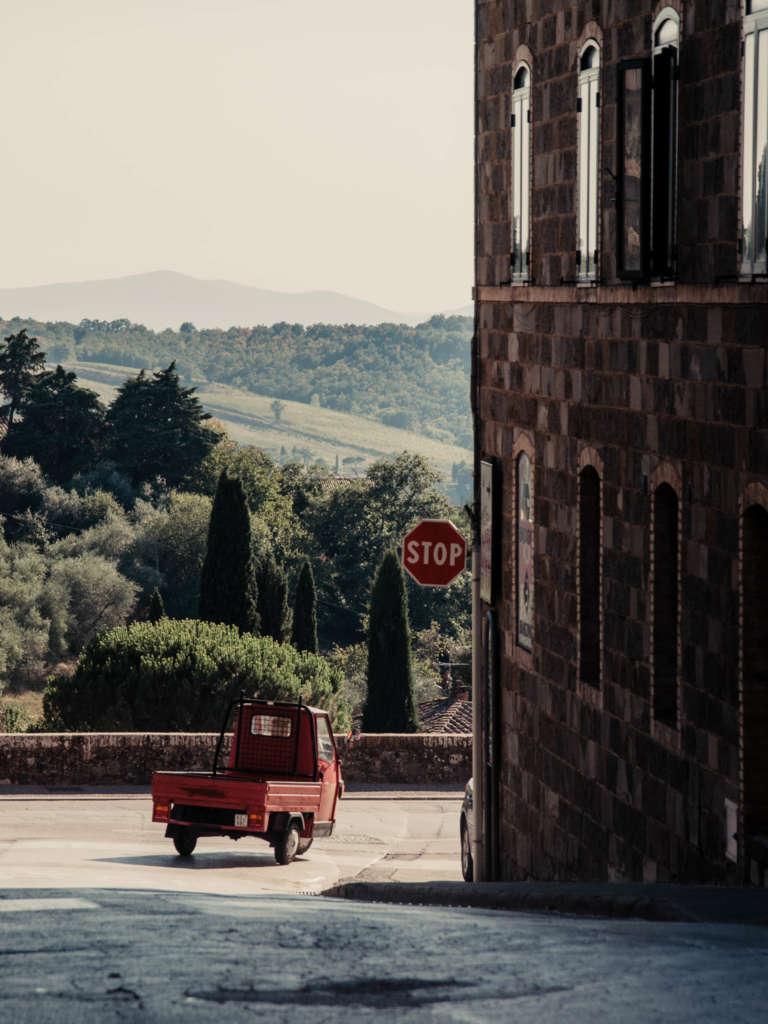 Eine rote dreirädrige Vespa, in Italien als Ape bekannt, biegt hinter einem Gebäude in eine Straße ein. Im Hintegrund leuchtet das satte Grün der toskanischen Zypressen, die jeden Toskana-Urlauber verzaubern.