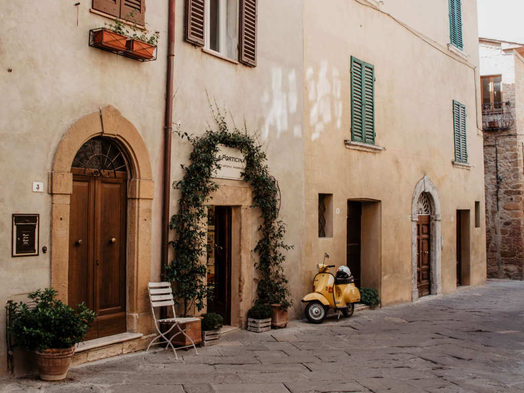 Eine gelbe Vespa steht an ein Sandsteinhaus gelehnt, die Hauswand zieren Fenster mit grünen Fensterläden, schwere Holztüren und ein Pflanzenkranz um die Eingangstür gebunden.